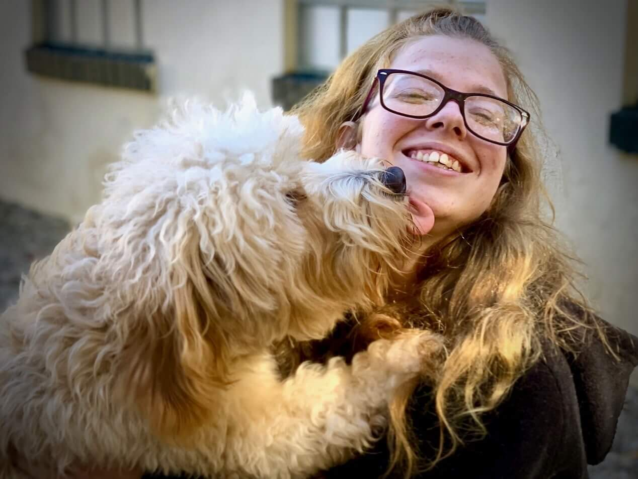 White Dog Licking Womans Face