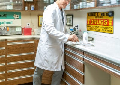 Dr. Rowan Counting Pills in his Pharmacy