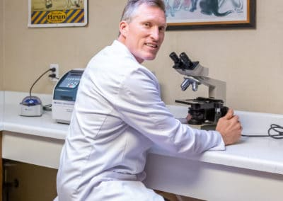 Dr. Rowan with Microscope in Laboratory